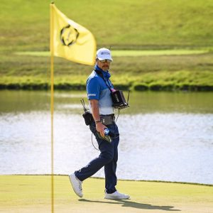 mark immelman golf broadcaster standing on putting green beside yellow flag